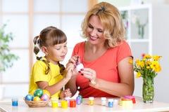 La mère heureuse enseigne la fille d'enfant à peindre des oeufs de pâques Photographie stock