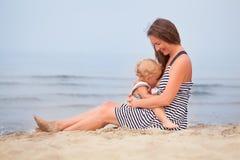 La mère heureuse et la petite fille vont le long du bord de la mer Photos stock