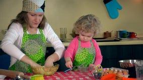 La mère heureuse et sa fille adorable malaxent la pâte ensemble et faisant le biscuit banque de vidéos