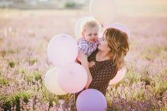 La mère heureuse et son petit le fils posant avec les ballons colorés dans une lavande mettent en place Photographie stock libre de droits