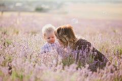 La mère heureuse et son petit le fils posant dans une lavande mettent en place Photos libres de droits