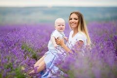 La mère heureuse et son petit le fils posant dans une lavande mettent en place Photos stock