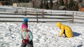 La mère heureuse joue dans le combat de Snowball avec sa fille dehors La femme dans le manteau jaune et la petite fille ont clips vidéos