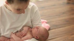 La mère heureuse regarde son bébé nouveau-né de sommeil nu avec amour clips vidéos