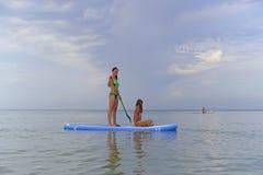 La mère heureuse roule sa fille sur un conseil pour SAP surfant sur la mer calme photos stock