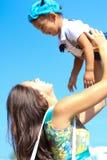 La mère jette son bébé dans le ciel Image stock