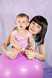 La mère avec la petite fille sur la grande boule Image stock