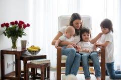 La mère, jouant avec son garçon d'enfant en bas âge et son frère plus âgé, a lu Photos libres de droits