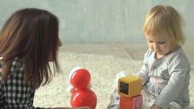 La mère joue avec le petit bébé avec des blocs et la poupée sur le tapis banque de vidéos