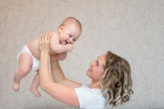 La mère joue avec son fils de bébé dans la chambre à coucher photos stock