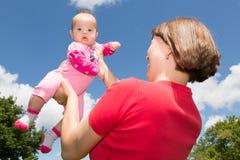 La mère juge sa fille de bébé haute dans le ciel Photographie stock