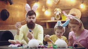 La mère, le père et le fils peignent des oeufs de pâques La famille heureuse se préparent à Pâques Port mignon de garçon de petit banque de vidéos