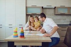 La mère, le père et l'enfant réunissent à la table image stock