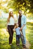 La mère, le père et la fille heureux dans le coucher du soleil en été se garent Photos libres de droits