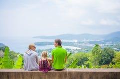 La mère, le père et la fille s'asseyent du côté et regardent autour du MOU Photos stock