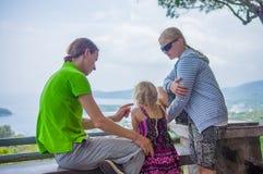 La mère, le père et la fille s'asseyent du côté et regardent autour du MOU Photographie stock libre de droits