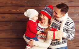 La mère, le père et le bébé heureux de famille avec des cadeaux de Noël courtisent dessus Photographie stock libre de droits