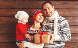 La mère, le père et le bébé heureux de famille avec des cadeaux de Noël courtisent dessus Image stock