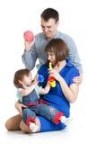 La mère, le père et le bébé jouent les jouets musicaux Photographie stock libre de droits