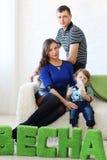La mère, le père et le petit fils s'asseyent sur le divan blanc Photographie stock