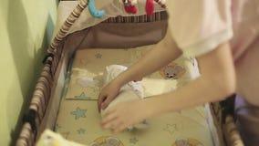 La mère met le bébé nouveau-né dans un berceau et couvert de couverture banque de vidéos
