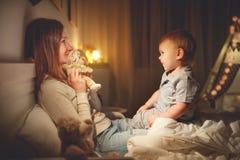 La mère met le fils de bébé pour dormir dans la soirée dans le lit Images stock