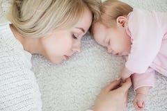 La mère met sa fille de bébé pour dormir Photos stock