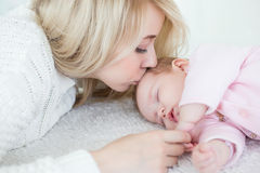 La mère met sa fille de bébé pour dormir Images libres de droits