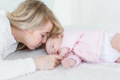La mère met sa fille de bébé pour dormir Photo libre de droits