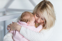 La mère met sa fille de bébé pour dormir Photographie stock libre de droits