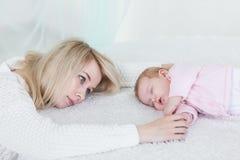 La mère met sa fille de bébé pour dormir Photos libres de droits