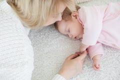 La mère met sa fille de bébé pour dormir Images stock