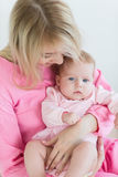 La mère met sa fille de bébé pour dormir Photo stock