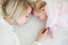 La mère met sa fille de bébé pour dormir Image stock