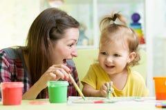 La mère mignonne enseignent son enfant de fille à peindre Images libres de droits