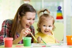 La mère mignonne enseignent son enfant de fille à peindre Image libre de droits