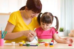 La mère mignonne enseignent son enfant de fille à peindre Images stock