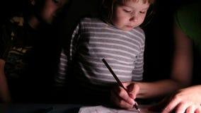 La mère montre à des enfants comment dessiner une fleur avec un crayon sur une feuille de papier, plan rapproché banque de vidéos