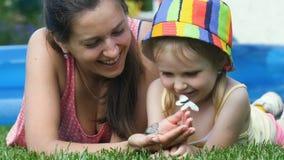 La mère montre des papillons dans des mains à sa fille clips vidéos