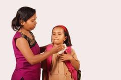 La mère nettoie le visage de la fille avec le tissu Fille dans l'uniforme scolaire Pune, maharashtra photographie stock libre de droits