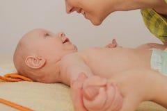 La mère ont plaisir à jouer avec ses cinq mois de bébé garçon Photographie stock libre de droits