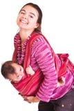 La mère oscille la chéri pour dormir dans l'élingue Photos stock