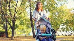 La mère porte son fils dans un landau en parc d'automne dans au ralenti 1920x1080 clips vidéos