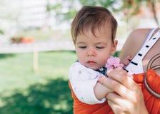 La mère portent un bébé infantile dans la bride d'enveloppe en parc printemps Concept du parenting naturel photos libres de droits