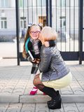 La mère prend sa fille d'école, embrasse la fille, concept de la famille Image libre de droits