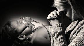 La mère prie pour la santé de la fille malade Photo stock
