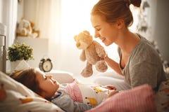 La mère réveille sa fille dans le lit dans le matin Photo libre de droits