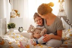 La mère réveille sa fille dans le lit dans le matin Photographie stock libre de droits