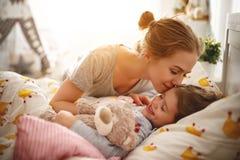 La mère réveille sa fille dans le lit dans le matin Photographie stock