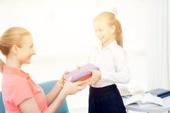 La mère rassemble sa fille à l'école La mère aide à rassembler les manuels du ` s de fille à l'école Photographie stock